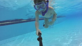 Το μικρό αγόρι με τη μάσκα και κολυμπά με αναπνευτήρα κολυμπώντας στη λίμνη απόθεμα βίντεο