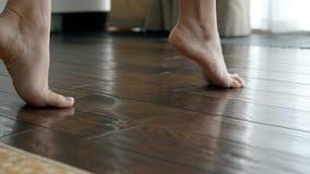 Το μικρό ελκυστικό πόδι είναι στο σκοτεινό καφετί ξύλινο παρκέ απόθεμα βίντεο