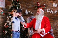 Το μικρό ενεργητικό αγόρι παίζει το ενδιαφέρον παιχνίδι στα γυαλιά εικονικού Στοκ Εικόνα