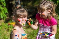 Το μικρό ευτυχές παιχνίδι αδελφών με τα χρώματα στο πάρκο, παιδιά παίζει, χρώμα παιδιών μεταξύ τους Στοκ εικόνες με δικαίωμα ελεύθερης χρήσης