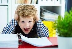 Το μικρό καυκάσιο σγουρό αγόρι άρπαξε το κεφάλι του καθμένος Στοκ φωτογραφία με δικαίωμα ελεύθερης χρήσης