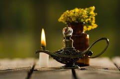 Το μικρό καφετί μπουκάλι ιατρικής για τους μάγους θεραπεύει, λαμπτήρας τύπων Aladin και άσπρη συνεδρίαση κεριών κεριών στην ξύλιν Στοκ εικόνα με δικαίωμα ελεύθερης χρήσης