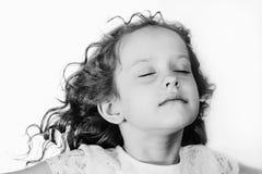 Το μικρό κορίτσι έκλεισε τα μάτια της και αναπνέει το καθαρό αέρα Ο Μαύρος στοκ εικόνα