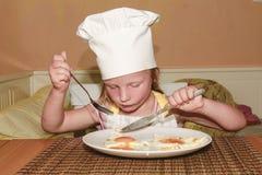 Το μικρό κορίτσι έχει ένα πρόχειρο φαγητό Το μικρό κορίτσι τρώει το ζαμπόν και τα αυγά Το χαριτωμένο κορίτσι έντυσε όπως έναν αρχ Στοκ Εικόνες