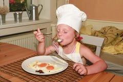 Το μικρό κορίτσι έχει ένα πρόχειρο φαγητό Το μικρό κορίτσι τρώει το ζαμπόν και τα αυγά Το χαριτωμένο κορίτσι φορά το κοστούμι αρχ Στοκ Φωτογραφίες