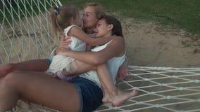 Το μικρό κορίτσι αγκαλιάζει ήπια mom και αδελφή στο βίντεο μήκους σε πόδηα αποθεμάτων αιωρών φιλμ μικρού μήκους