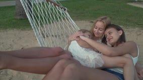 Το μικρό κορίτσι αγκαλιάζει ήπια mom και αδελφή στο σε αργή κίνηση βίντεο μήκους σε πόδηα αποθεμάτων αιωρών απόθεμα βίντεο
