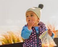 Το μικρό κορίτσι δαγκώνει σκεπτικά Στοκ Εικόνα