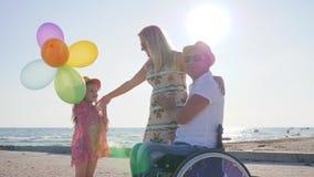 Το μικρό κορίτσι ακούει μητέρα και πατέρας με την αναπηρία στην καρέκλα ροδών στην παραλία το καλοκαίρι tim απόθεμα βίντεο