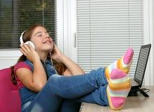 Το μικρό κορίτσι ακούει μουσική από το lap-top Στοκ Εικόνες