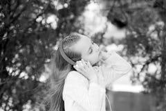 Το μικρό κορίτσι ακούει μουσική στο θερινό πάρκο Ήχος και mp3 μελωδίας Το παιδί απολαμβάνει τη μουσική στα ακουστικά υπαίθρια Παι Στοκ Εικόνες