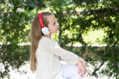 Το μικρό κορίτσι ακούει μουσική στο θερινό πάρκο Το παιδί απολαμβάνει τη μουσική στα ακουστικά υπαίθρια Παιδί μόδας και σύγχρονη  Στοκ εικόνες με δικαίωμα ελεύθερης χρήσης