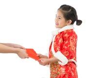Το μικρό κορίτσι λαμβάνει τα κόκκινα χρήματα τύχης φακέλων Στοκ Φωτογραφία