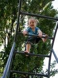 Το μικρό κορίτσι αναρριχείται στα σκαλοπάτια στο υπόβαθρο δέντρων στοκ εικόνα με δικαίωμα ελεύθερης χρήσης