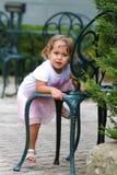 το μικρό κορίτσι αναρριχείται στην καρέκλα στοκ εικόνες