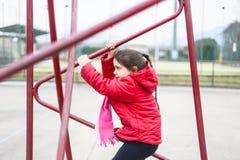 Το μικρό κορίτσι αναρριχείται στο πλαίσιο σιδήρου ενός καλαθιού για το παιχνίδι καλαθοσφαίρισης Στοκ Φωτογραφία