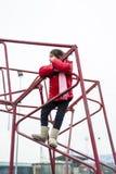 Το μικρό κορίτσι αναρριχείται στο πλαίσιο σιδήρου ενός καλαθιού για το παιχνίδι καλαθοσφαίρισης Στοκ φωτογραφίες με δικαίωμα ελεύθερης χρήσης