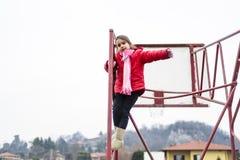 Το μικρό κορίτσι αναρριχείται στο πλαίσιο σιδήρου ενός καλαθιού για το παιχνίδι καλαθοσφαίρισης Στοκ εικόνα με δικαίωμα ελεύθερης χρήσης