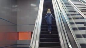 Το μικρό κορίτσι ανεβαίνει την κυλιόμενη σκάλα απόθεμα βίντεο