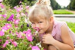 Το μικρό κορίτσι απολαμβάνει τη μυρωδιά των λουλουδιών Στοκ Εικόνα