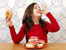 Το μικρό κορίτσι απολαμβάνει στα donuts Στοκ φωτογραφία με δικαίωμα ελεύθερης χρήσης