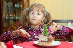 Μικρό κορίτσι που τρώει ένα κέικ Στοκ εικόνες με δικαίωμα ελεύθερης χρήσης