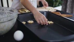 Το μικρό κορίτσι βάζει ένα ακατέργαστο μπισκότο στο δίσκο ψησίματος Το παιδί, μαζί με τη μητέρα του, ψήνει τα μπισκότα μπισκότων  φιλμ μικρού μήκους