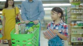 Το μικρό κορίτσι βάζει τα λουκάνικα στο καροτσάκι αγοράς απόθεμα βίντεο
