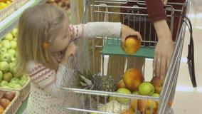 Το μικρό κορίτσι βάζει τα φρούτα στο καροτσάκι Στοκ φωτογραφία με δικαίωμα ελεύθερης χρήσης