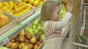 Το μικρό κορίτσι βάζει τα φρούτα στο καροτσάκι Στοκ Εικόνες