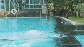 Το μικρό κορίτσι βουτά στο νερό της υπαίθριας πισίνας σε σε αργή κίνηση απόθεμα βίντεο