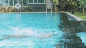 Το μικρό κορίτσι βουτά στο νερό της υπαίθριας πισίνας σε σε αργή κίνηση φιλμ μικρού μήκους