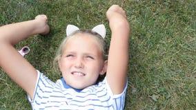 Το μικρό κορίτσι βρίσκεται θερινό πορτρέτο χλόης απόθεμα βίντεο