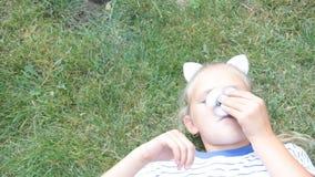 Το μικρό κορίτσι βρίσκεται κλώστης θερινού πορτρέτου χλόης, παιχνίδι απόθεμα βίντεο