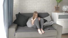 Το μικρό κορίτσι βρίσκεται στο κρεβάτι και εξετάζει το smartphone της απόθεμα βίντεο