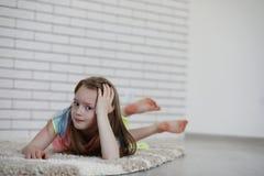 Το μικρό κορίτσι βρίσκεται στο πάτωμα Στοκ εικόνες με δικαίωμα ελεύθερης χρήσης