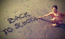 Το μικρό κορίτσι γράφει πίσω στο σχολείο στην παραλία ι Στοκ Φωτογραφία