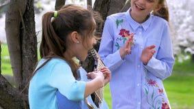 Το μικρό κορίτσι γρατζουνά στην κιθάρα ενώ η φίλη της που στέκεται που χτυπά τη μουσική ακούσματος χεριών του θαυμάσια ημέρα άνοι απόθεμα βίντεο