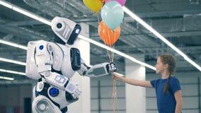 Το μικρό κορίτσι δίνει τα μπαλόνια σε έναν ανθρώπινος-όπως cybord απόθεμα βίντεο