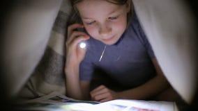 Το μικρό κορίτσι διαβάζει ένα βιβλίο κάτω από ένα κάλυμμα με έναν φακό σε ένα σκοτεινό δωμάτιο τη νύχτα φιλμ μικρού μήκους