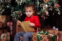 Το μικρό κορίτσι διαβάζει τις ιστορίες σε ένα βιβλίο από ένα χριστουγεννιάτικο δέντρο Κόκκινο πουκάμισο των πυτζαμών Κάθεται στα  Στοκ Φωτογραφίες