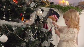 Το μικρό κορίτσι διακοσμεί ένα χριστουγεννιάτικο δέντρο απόθεμα βίντεο