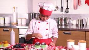 Το μικρό κορίτσι διακοσμεί muffin το μούρο απόθεμα βίντεο