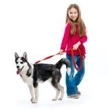 Το μικρό κορίτσι είναι με το γεροδεμένο σκυλί Στοκ Φωτογραφία