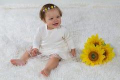 Το μικρό κορίτσι είναι συνεδρίαση γέλιου στο μαλακό άσπρο τάπητα Στοκ Φωτογραφίες