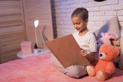 Το μικρό κορίτσι, εγγονή διαβάζει το βιβλίο τη νύχτα στο σπίτι στοκ φωτογραφίες με δικαίωμα ελεύθερης χρήσης
