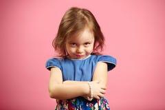 Το μικρό κορίτσι εξετάζει τη κάμερα με μια ματιά, εκφράζει τη δυσαρέσκεια ή ο θυμός, καταδεικνύει το χαρακτήρα της στοκ φωτογραφία