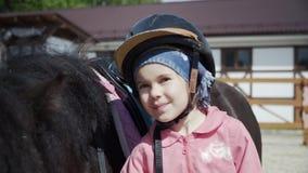 Το μικρό κορίτσι εξετάζει τη κάμερα, την τοποθέτηση με το μαύρο πόνι και το χαμόγελο φιλμ μικρού μήκους
