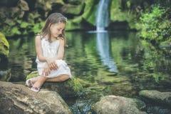 Το μικρό κορίτσι εξετάζει τη συνεδρίαση νερού δίπλα στο κρεβάτι ενός rive στοκ φωτογραφία με δικαίωμα ελεύθερης χρήσης