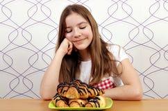 Το μικρό κορίτσι εξετάζει το croissant στοκ εικόνα με δικαίωμα ελεύθερης χρήσης